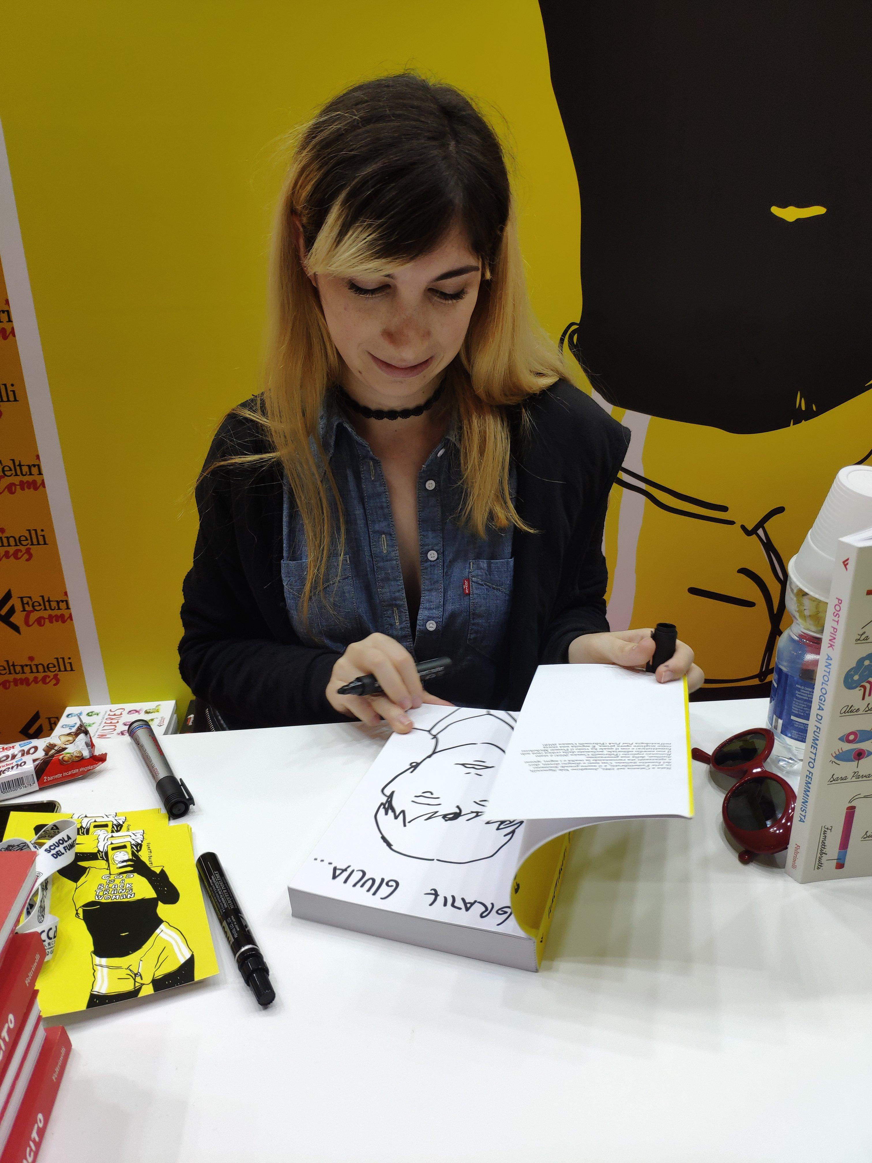 Mio Caro Fumetto - Lucca Comics & Rain 2019 - Josephine Yole Signorelli mentre disegna la dedica sulla mia copia di P., la mia adolescenza trans.