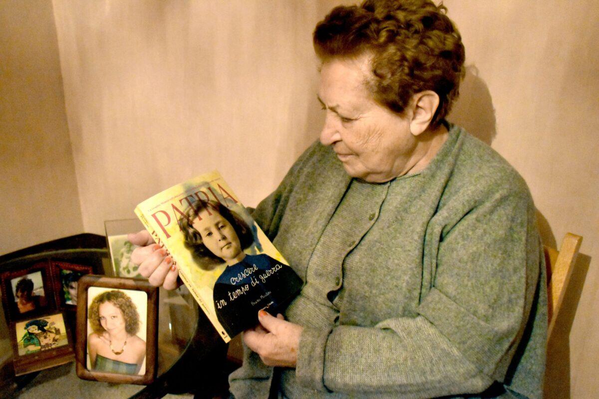 Mio caro fumetto... - Grazia Mapelli stringe una copia di Patria, crescere in tempo di guerra. In cornice la foto della nipote Bruna Martini